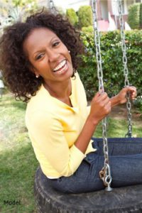 Woman sitting on a tire swing