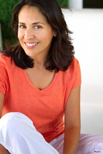 Woman sitting & smiling