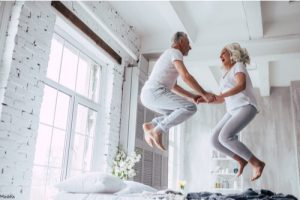 Man and woman jumping on the bed