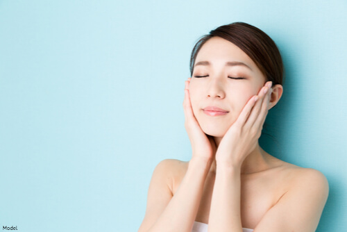 Woman touching her smooth skinned face