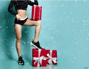 Woman wearing workout clothes with Christmas gifts